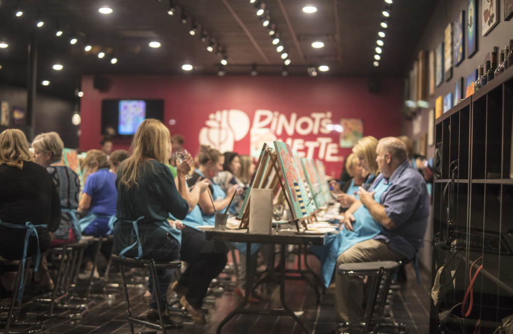 large group of adults painting inside Pinot's Palette